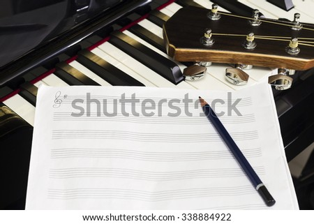 Music,Staff Sheet and Pencil  with Guitar on Piano  - stock photo