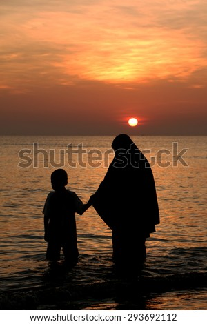 Muslim woman hold hand  with love a son  walking careful during sunset on the beach ocean wave silhouette  - stock photo