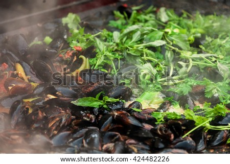 Mussels cooked with white and red wine sauce at mussels festival - stock photo