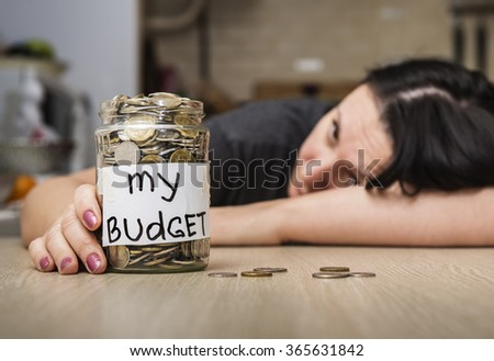 My budget. Coins in glass money jar, woman in the background - stock photo