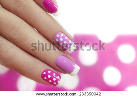 Nail design with white dots on the French manicure with pink varnish of various shades. - stock photo