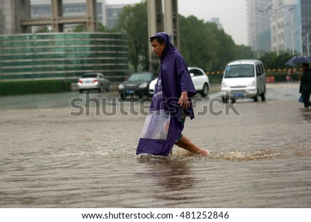 NANCHANG,CHINA - June29, 2013:Cars travel through a flooded road caused by heavy rain in Nanchang city, pedestrians wading across the river,east China's Jiangxi province, 29 June 2013.