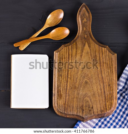 napkin, a recipe book, a cutting board and a wooden spoon on a black background - stock photo