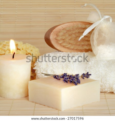 Natural cleansing skincare beauty products with lit by a candle over bamboo background. - stock photo