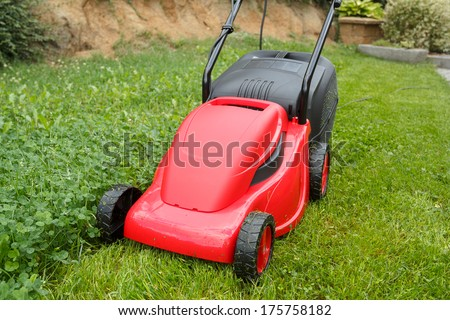 new lawnmower on green grass in cloudy day - stock photo