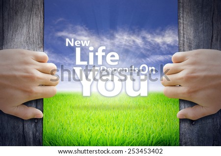 """""""New life depend on you"""" Motivational quotes. Hands opening a wooden door then found a texts floating among new world as green grass field, Blue sky and the Sunrise. - stock photo"""