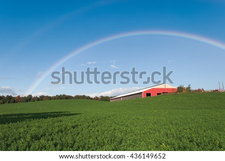 New Rainbow Against Blue Sky over Field and Barn - stock photo