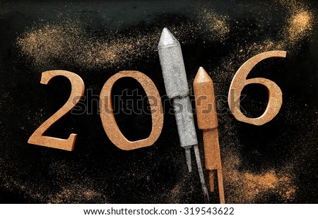 2016 New Year background with festive gold and silver rockets forming part of the date over a dark background with sparkling glitter trails - stock photo