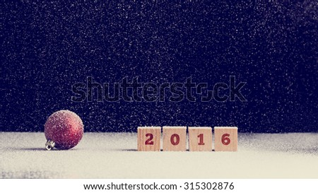 2016 New Year background with snow falling onto a red Christmas bauble and row of four wooden blocks with the date numerals - 2016 - over dark background with copyspace for your seasonal greeting. - stock photo