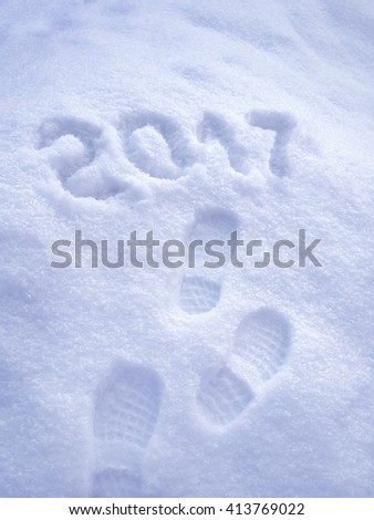 2017 New Year greeting card, 2017 new year, foot step prints in snow, happy new year 2017 concept - stock photo