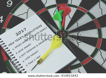 2017 new year's resolutions on notepad with darts on bulls eye, retro style - stock photo