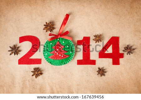 2014 new year with christmas toy from felt and star anise around on paper background - stock photo