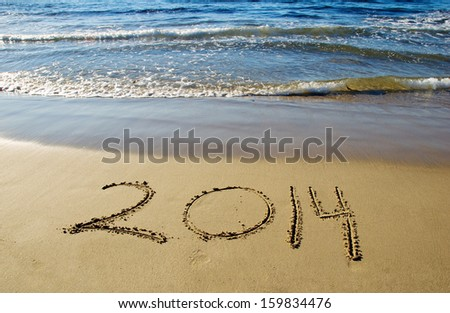 2014 new year written in sand on the beach - stock photo