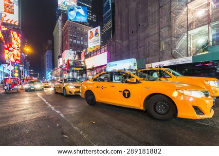 NEW YORK CITY - JUNE 12, 2015: Yellow taxi cabs and glowing electric signs near Times Square - stock photo