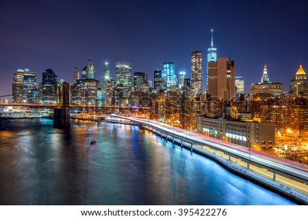 New York City night scene with Manhattan skyline and Brooklyn Bridge, USA