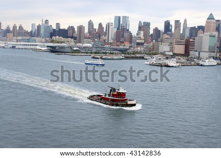 New York famous skyline and boat docks along the Hudson River with tug boat or pilot boat in the forefront - stock photo