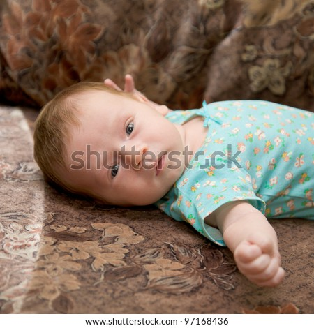 Newborn baby lying on the couch and looking into the camera - stock photo