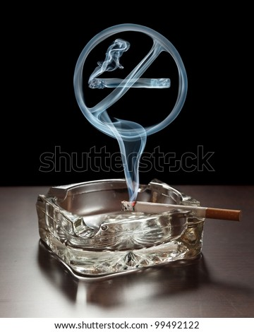 """No smoking"" smoke sign rising from a cigarette in an ashtray. - stock photo"