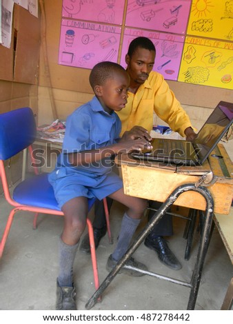 Norton,Zimbabwe, October 9 2015. A  primary school kid in  a  classroom getting  instructions  on how   to  use a  computer  from  his  teacher.