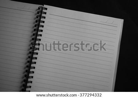 Notebook on dark background. - stock photo