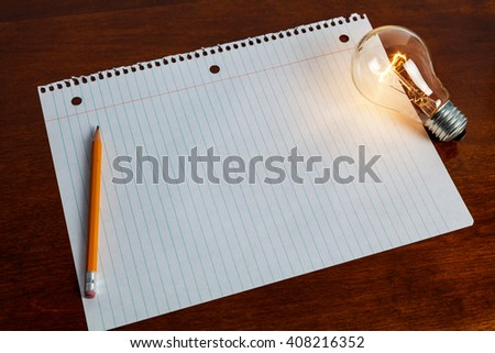 notebook paper and light bulb, business education concept.