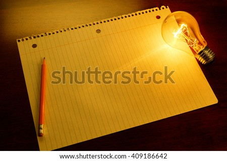 notebook paper and light bulb, business education concept. - stock photo