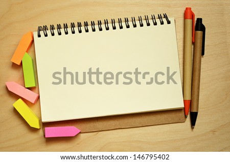 Notebook, stickers and pens on wooden desk - stock photo
