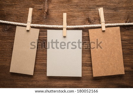 Notes and a clothes pegs on wooden background  - stock photo