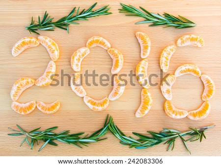 2016 number written with oranges sections and rosemary sprigs on wooden background - stock photo