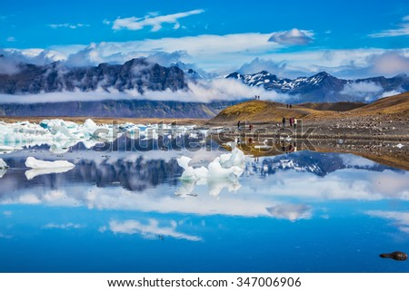 Ocean Bay is surrounded by volcanic mountains and glaciers. Icebergs and ice floes are reflected in the mirrored water. Ice lagoon in Iceland - stock photo