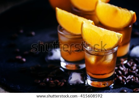 �¡ocktail bumblebee with orange juice, caramel syrup and espresso coffee with ice cubes, black background, selective focus, shallow depth of field