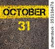 31 October calendar day written over road marking yellow paint line - stock photo