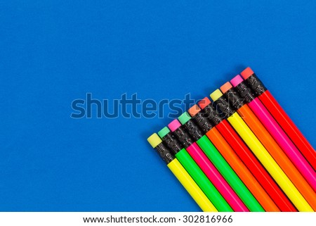 Office or back to school supplies consisting of colorful pencils in lower right corner on blue background.   - stock photo