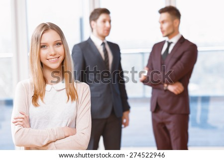 Office workers. Blond young business woman standing in foreground smiling  , her co-workers discussing business matters in the background - stock photo