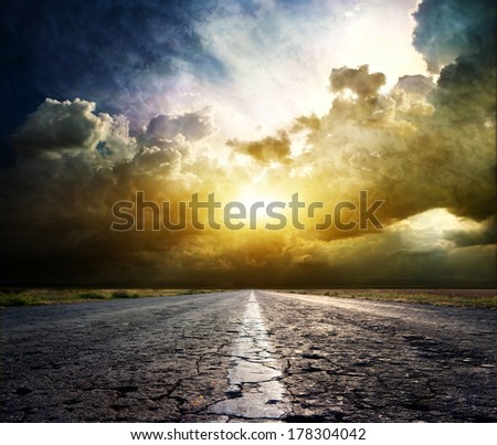 Old asphalt road on the background of Dramatic sunset - stock photo