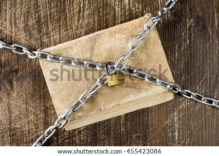 Old book with chain and padlock on wooden background. - stock photo