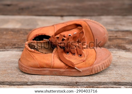 Old brown sneakers , Students sneakers on wooden background - stock photo
