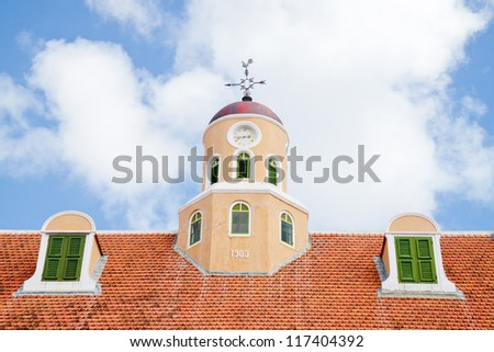 Old clock roof tower with weather cockerel and two dormers with green shutters on red stone tile roof with blue sky and white clouds in the background. - stock photo