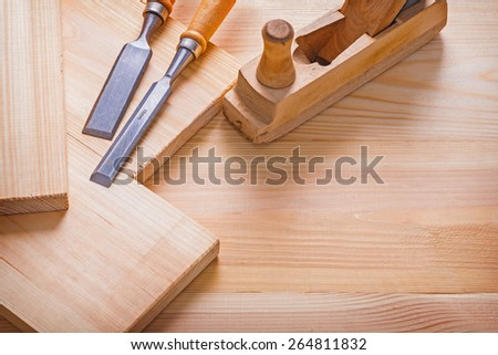 old fashioned woodworkers plane carpentry chisel and wooden planks construction concept