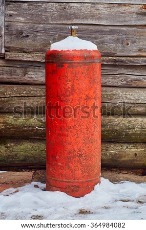 Old gas bottle near a wall of wooden house                               - stock photo