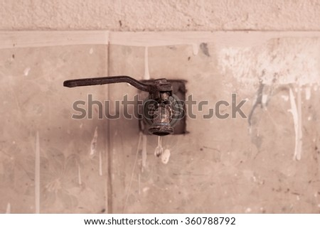 old profile of a bronze metallic faucet with water drop