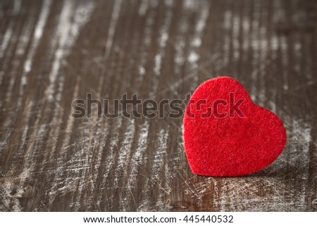 Old scratched wooden background with a small red heart - stock photo