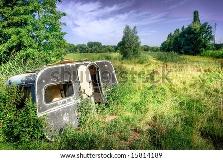 old,worn down caravan in nature. High dynamic range image. - stock photo
