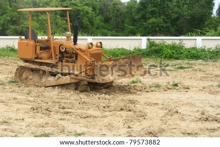 Old yellow bulldozer at a construction site - stock photo