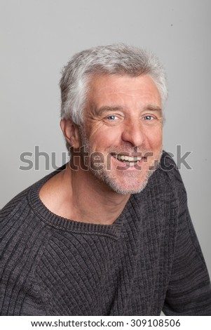older gray-haired man sitting smiling looking at the camera grey eyes - stock photo