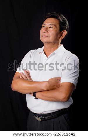 older man in a white t-shirt on a black background