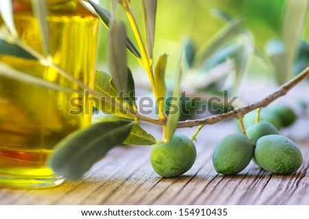 olive oil on old wooden table and an olive branch