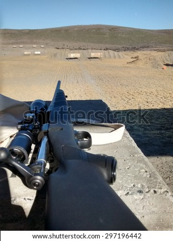 30-06 on a rifle range. This is rifle is colored black loaded with the bolt out. The rifle is pointing down range - stock photo
