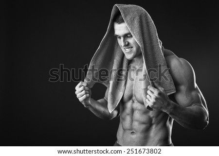 on dark background.Fitness man holding a orange  towel against dark background.Strong Athletic Man Fitness Model Torso showing  abs. holding towel. - stock photo