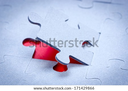 One piece of jigsaw revealing red background - stock photo